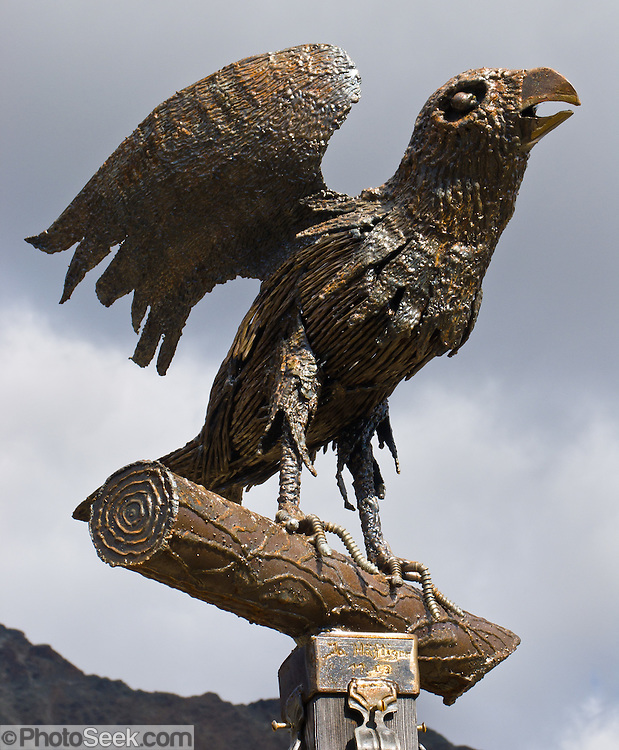 """Brass crow sculpture, Pontresina, in Upper Engadine, Switzerland, in the Alps, Europe. The Swiss valley of Engadine translates as the """"garden of the En (or Inn) River"""" (Engadin in German, Engiadina in Romansh, Engadina in Italian)."""