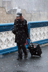 © Licensed to London News Pictures. 10/12/2017. London, UK. A woman walks across Tower Bridge during heavy snow fall. Heavy snow has fallen across the UK this morning. Photo credit: Vickie Flores/LNP