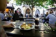"""Brotzeit mit einem dunklen Bier im Biergarten von """"U Fleku"""" in der Prager Innenstadt."""