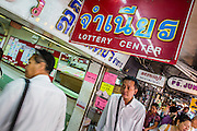 04 JANUARY 2012 - BANGKOK, THAILAND:  People walk past a lottery ticket shop on  Sukhumvit Soi 77 in Bangkok. About 20 million Thais, nearly ? of the country's 65 million people, play lottery type games. The lotteries were brought to Thailand two hundred years ago by Chinese immigrants. Lottery agents are usually friends who collect bets but do not ask for money before the drawing. The lottery shops are close to Wat Mahabut and many people go the temple to see the fortune tellers and pray at the shrines there for guidance on the numbers to play in the lottery games.   PHOTO BY JACK KURTZ