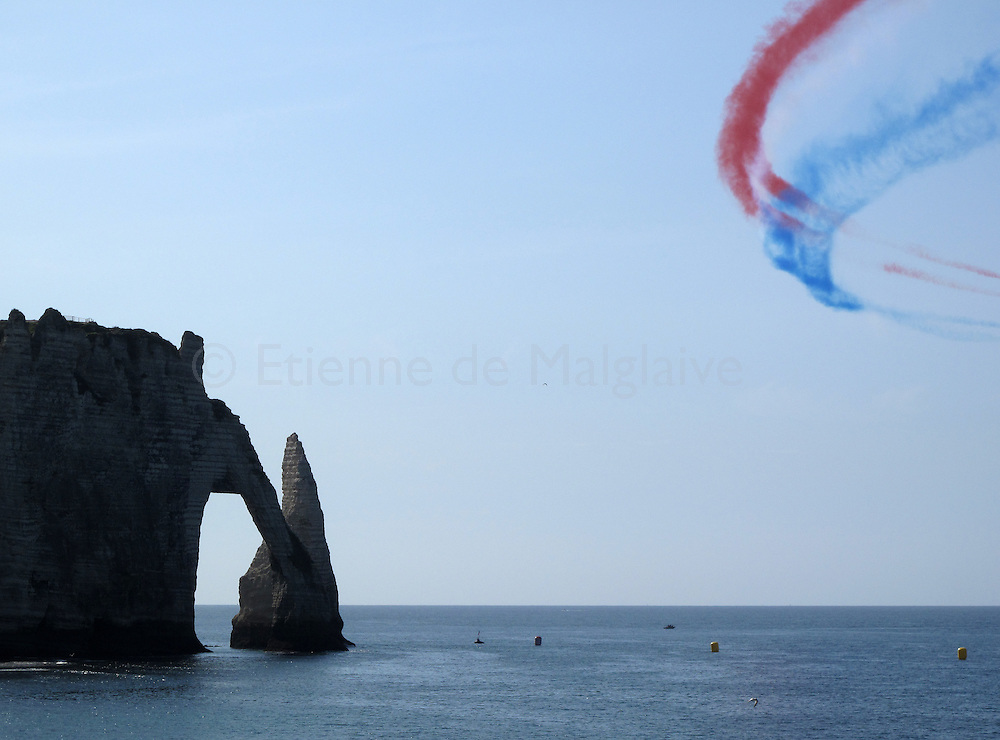 """Coloured smoke trails from French air forces aerobatic team """"La Patrouille de France"""" during an airshow rehearsal over the scenic cliff of Etretat, a Normandy seaside town in France. 23 September 2011."""
