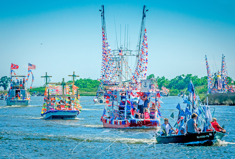 Decorated boats travel down the bayou during the 66th annual Blessing of the Fleet in Bayou La Batre, Alabama, May 3, 2015. The first fleet blessing was held by St. Margaret's Catholic Church in 1949, carrying on a long European tradition of asking God's favor for a bountiful seafood harvest and protection from the perils of the sea. The highlight of the event is a blessing of the boats by the local Catholic archbishop and the tossing of a ceremonial wreath in memory of those who have lost their lives at sea. The event also includes a land parade and a parade of decorated boats that slowly cruise through the bayou. (Photo by Carmen K. Sisson/Cloudybright)
