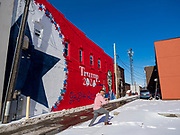 01 FEBRUARY 2020 - BOONE, IOWA: A man walks in the snow to photograph a mural supporting President Donald Trump in downtown Boone, IA. Carl McKnight, a Boone realtor and Donald Trump supporter, commissioned the mural, which he calls nothing more than a campaign sign. Some in Boone, a community about 45 miles northwest of Des Moines, are concerned that the mural, which dominates a new park and bandshell in Boone, is not appropriate in a space shared by all people. A Boone city councilperson said people who donated to the fund to build the park have asked for their donations back. McKnight said the mural will stay up until at least election day.    PHOTO BY JACK KURTZ