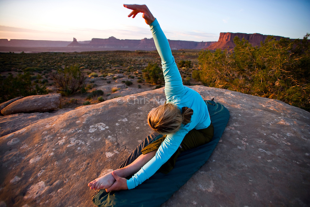Katie Caviccio does some stretching at camp after a day of mountain biking on the White Rim Trail, Canyonlands National Park, Utah