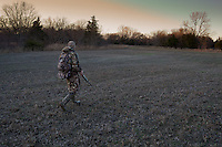 MOSSBERG SHOTGUN HUNTER WEARING REALTREE AP CAMOUFLAGE WALKING THROUGH AN OPEN FIELD