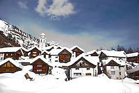 Ticino, Southern Switzerland. The traditional houses of the alpine village of Bosco Guirin covered in snow.