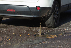 Water splashes as a car bumps its way through a deep pothole on Brondesbury Road in up-market Queens Park in west London as the recent cold, wet weather has given rise to the increase in potholes and road surface deterioration in the capital. London, March 28 2018.