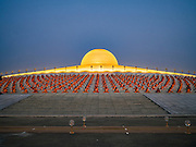 "22 FEBRUARY 2016 - KHLONG LUANG, PATHUM THANI, THAILAND: Buddhist monks sit around the chedi during Makha Bucha Day at Wat Phra Dhammakaya.  Makha Bucha Day is a public holiday in Cambodia, Laos, Myanmar and Thailand. Many people go to the temple to perform merit-making activities on Makha Bucha Day, which marks four important events in Buddhism: 1,250 disciples came to see the Buddha without being summoned, all of them were Arhantas, Enlightened Ones, and all were ordained by the Buddha himself. The Buddha gave those Arhantas the principles of Buddhism, called ""The ovadhapatimokha"". Those principles are:  1) To cease from all evil, 2) To do what is good, 3) To cleanse one's mind. The Buddha delivered an important sermon on that day which laid down the principles of the Buddhist teachings. In Thailand, this teaching has been dubbed the ""Heart of Buddhism."" Wat Phra Dhammakaya is the center of the Dhammakaya Movement, a Buddhist sect founded in the 1970s and led by Phra Dhammachayo. The temple is famous for the design of its chedi, which some have likened to a flying saucer or UFO.           PHOTO BY JACK KURTZ"