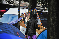 Refugees who have settled near Place de Stalingrad on Avenue de Flandres in Paris, France, eat food on October 28, 2016. Most of the migrants are Eritrean, Somalian and Sudanese. Humanitarian aid group ADRA France facilitates the resettlement. The number of migrants in makeshift camps increased in the French capital after Calais' jungle closure. Photo by Yann Korbi/ABACAPRESS.COM