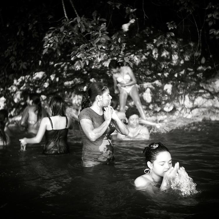 Schoolgirls bathe in hot springs in the Rio Dulce River in Guatemala.