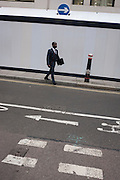 Londoners walk through Coleman Street, following the directions of opposing arrows in the City of London, England.