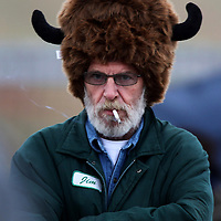 Jim Williams of El Paso, Texas tries to stay warm during the annual bison roundup at Custer State Park in western South Dakota.