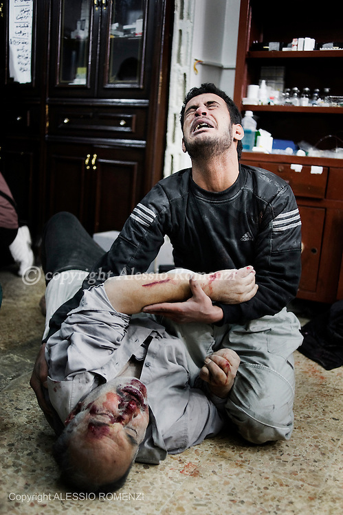 SYRIA, HOMS, Baba Amro: A Syrian boy hugs a seriously wounded  man in a house used as hospital in Baba Amro, southern neighbouhood of Homs on February 06, 2012.  ALESSIO ROMENZI