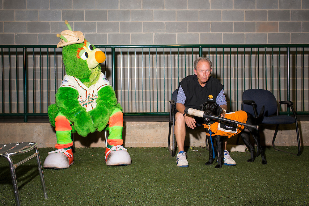 Guilford, the Greensboro Grasshopper mascot, with General Manager Donald Moore and Miss Lou Lou Gehrig, one of three bat dogs at NewBridge Bank Park, Greensboro, North Carolina, Monday, June 21, 2014.