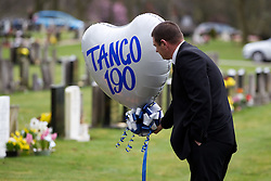 "© licensed to London News Pictures. Stafford, UK  17/03/2012. A mourner holds on to a balloon reading ""Tango 190"", PC Rathband's call sign, after the funeral of PC David Rathband. Photo credit should read Joel Goodman/LNP"