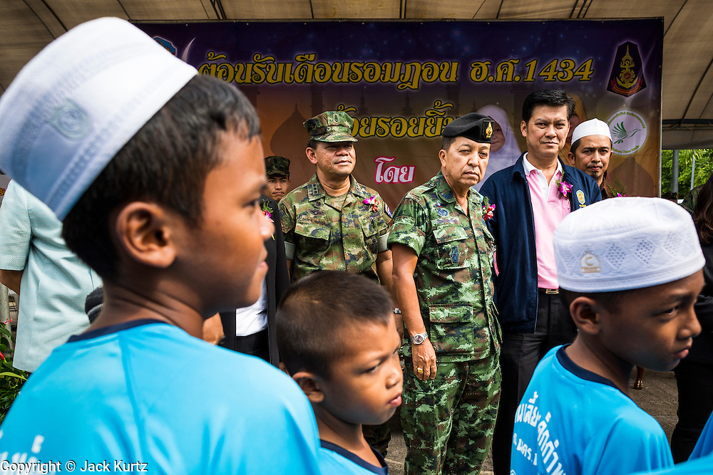 07 JULY 2013 - NARATHIWAT, NARATHIWAT, THAILAND:  Maj. Gen. PHISIT SITTHISAN, commander of the Narathiwat Task Force, talks to Thai Muslim youths during a Thai Marine civil affairs program. Royal Thai Marines in Narathiwat province held a special ceremony Sunday in advance of Ramadan. They presented widows, orphans and indigent people with extra rice and food as a part of the Thai government's outreach to resolve the Muslim insurgency that has wracked southern Thailand since 2004. The Holy Month of Ramadan starts on about July 9 this year. Muslims are expected to fast from dawn to dusk, engage in extra prayers, recitation of the Quran and perform extra acts of charity during Ramadan. It is the holiest month of the year for Muslims.   PHOTO BY JACK KURTZ