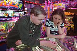 Homeless teenage boy and girl leaning against slot machine in seaside arcade,