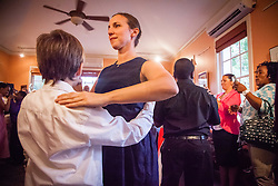 """Teaching artist Mary Capellas dances with her student during a Waltz.  Students of Dancing Classrooms of the Virgin Islands dance at a reception for their parents, family community, and school partners at the Virgin Islands Council on the Arts.  Students spent weeks learning the Tango, Foxtrot, Meringue, Swing, Rumba, and Waltz that will culminate in """"Colors of the Rainbow"""" team match competition at Reichhold Center for the Arts on Saturday, May 9, 2015.  St. Thomas, USVI.  8 May 2015.   © Aisha-Zakiya Boyd"""