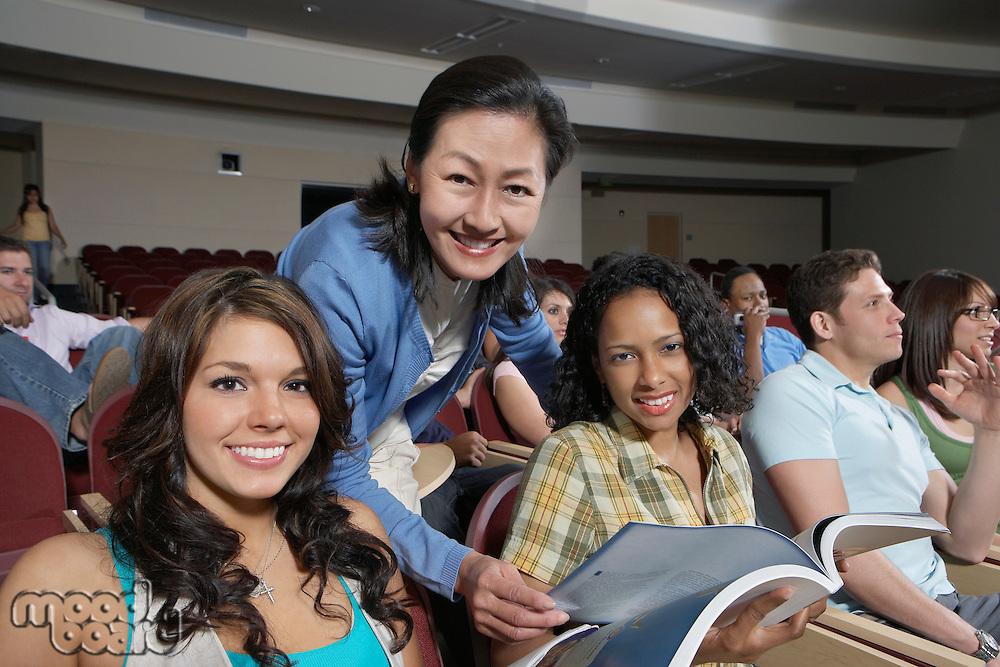 Female teacher assisting female students in class, portrait