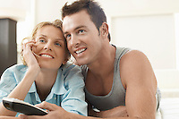 Couple on bed watching television man holding remote control