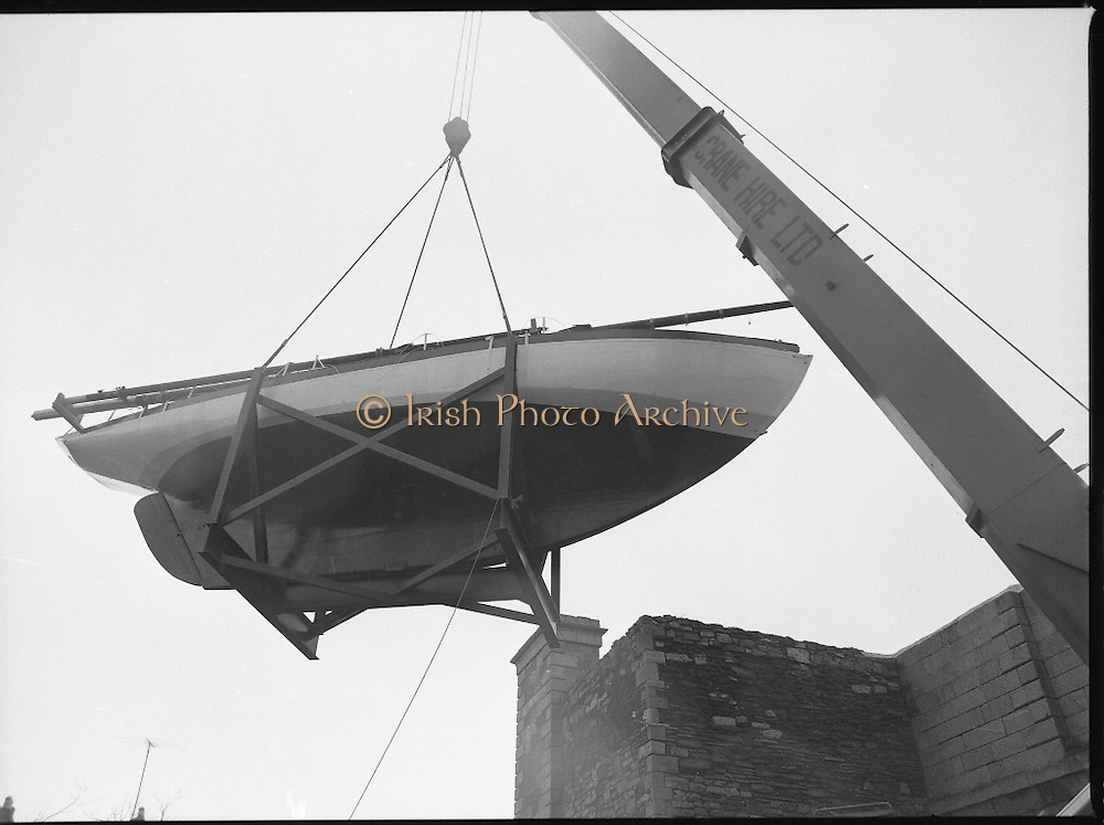 """The """"Asgard """" at Kilmainham Jail..1979..01.04.1979..04.01.1979..1st April 1979..The historic yacht """"Asgard"""" owned by Erskine Childers was brought to Kilmainham Jail,Dublin. The vessel had to be hoisted ,by crane,over the outer wall of the jail. It was placed as part of a future exhibition to be set up by The National Museum..Image of the crane slowly lifting the yacht up over the jail wall."""