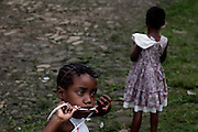 Two girls are playing on the streets of Roça  Monte Café', on the island of Sao Tome, Sao Tome and Principe, (STP) a former Portuguese colony in the Gulf of Guinea, West Africa.