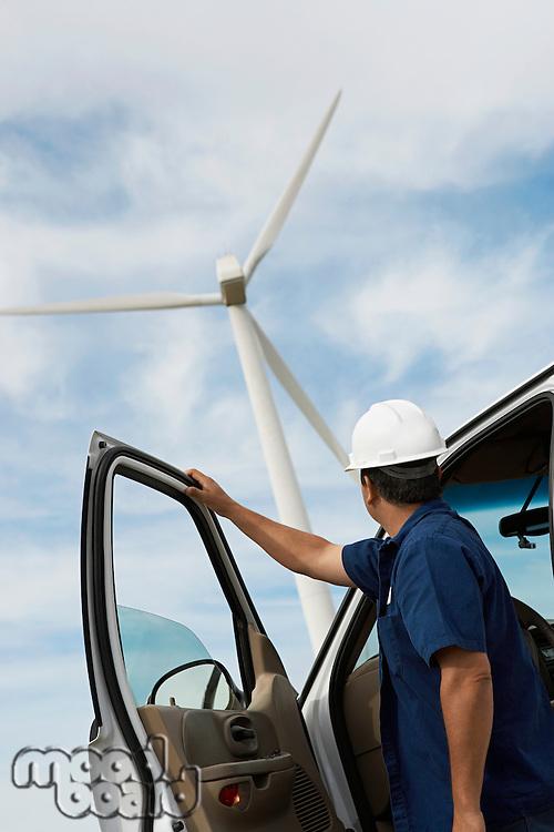 Engineer by car at wind farm