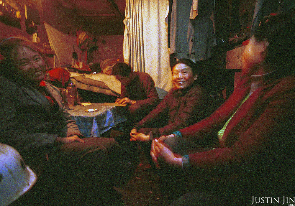 Migrant workers at the Beijing garbage dump enjoy the evening at their makeshift shelter next to the garbage dump. Because they all came from the same village one thousand miles away in Sichuan provine, these workers are very warm to one another...Picture taken March 1999.Copyright Justin Jin