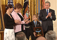 CAPTION: (Washington, D.C. : 4/04/2005) David Smith (cq), 11, holds the Medal of Honor presented to his father, Sgt. 1st Class Paul Smith, who was killed in Iraq, as his sister, Jessica Smith (cq), 18, left, mother, Birgit Smith (cq) and President George W Smith applaud during the ceremony in the East Room of the White House Monday 4/4/05.  STORY SUMMARY: Medal of Honor Presentation at the White House