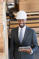 Portrait of African American male contractor using tablet PC with wooden planks in background