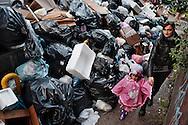 Napoli, Italia - 24 novembre 2010. Mamma e figlia camminano nel quartiere Vomero tra un enorme cumulo di rifiuti.Ph. Roberto Salomone Ag. Controluce.ITALY - Piles of uncollected garbage are seen downtown Naples on November 24, 2010.