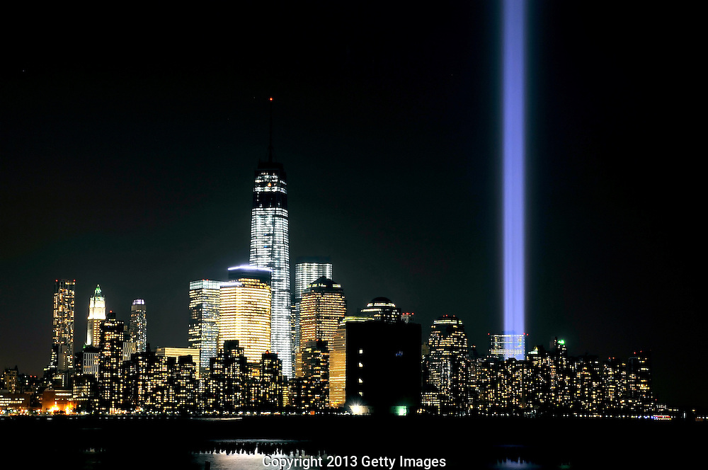 """HOBOKEN, NJ - SEPTEMBER 11:  The """"Tribute in Light"""" shines from the Manhattan skyline next to One World Trade Center to commemorate all those who were lost on 9/11 on September 11, 2013 in Hoboken, New Jersey. The lights are located at West and Morris streets in lower Manhattan. The nation is commemorating the anniversary of the 2001 attacks which resulted in the deaths of nearly 3,000 people after two hijacked planes crashed into the World Trade Center, one into the Pentagon in Arlington, Virginia and one crash landed in Shanksville, Pennsylvania. (Photo by Michael Bocchieri/Getty Images)"""
