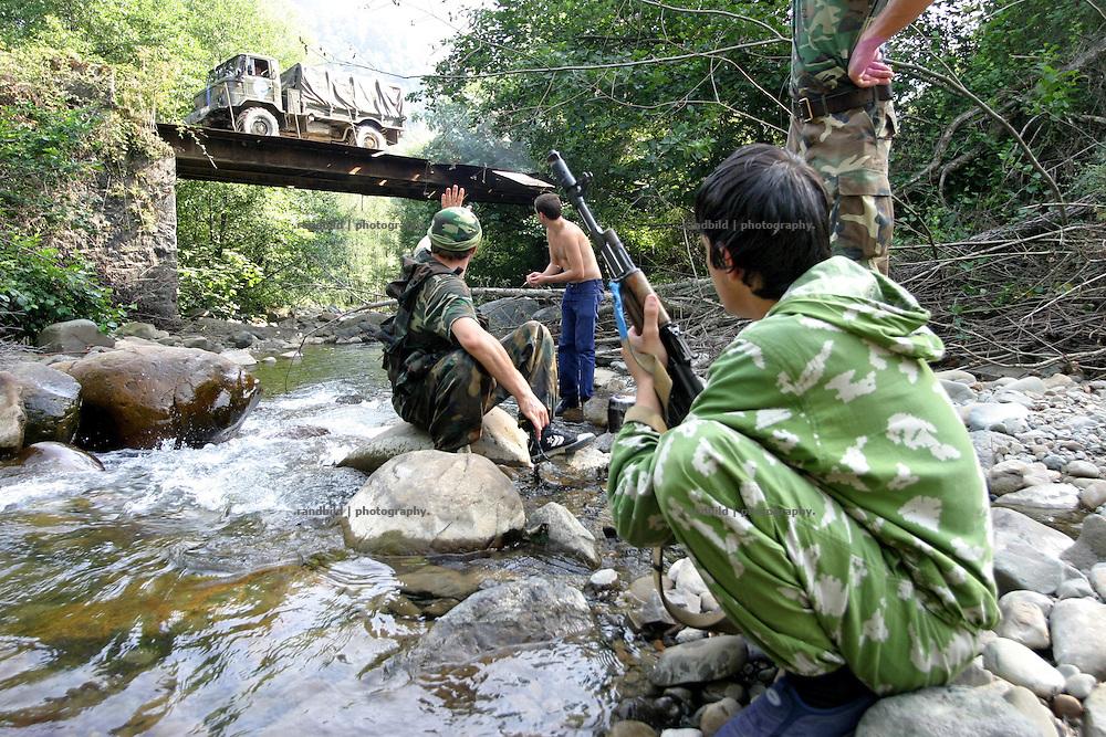 Georgien/Abchasien, Suchumi, 2006-08-28, Abchasische Soldaten erfrischen sich an einem Fluß im zwischen Abchasen und Georgiern umkämpften Kodorital . Abchasien erklärte sich 1992 unabhängig von Georgien. Nach einem einjährigen blutigen Krieg zwischen den Abchasen und Georgiern besteht seit 1994 ein brüchiger Waffenstillstand, der von einer UNO-Beobachtermission unter personeller Beteiligung Deutschlands überwacht wird. Trotzdem gibt es, vor allem im Kodorital immer wieder bewaffnete Auseinandersetzungen zwischen den Armeen der Länder sowie irregulären Kämpfern. (Abkhazian soldiers refreshing themselfs in the Kodori gorge, where abkhazian and georgian fighting each other. Abkhazia declared itself independent from Georgia in 1992. After a bloody civil war a UNO mission observing the ceasefire line between Georgia and Abkhazia since 1994. Nevertheless nearly every day armed incidents take place in the Kodori gorge between the both armys and unregular fighters )