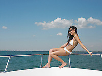 Young woman in bikini sitting on bow of yacht side view