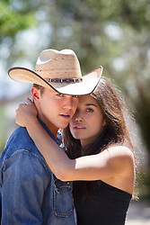 woman with her arm around a young cowboy outdoors