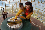 The Baiterek is the New Astana's main symbol and landmark. Visitors can lay their hand in a golden imprint of President Nursultan Nasarbaev's right hand. Doing so, they have one wish supposed to come true.  Janna is trying it out with her little kid.