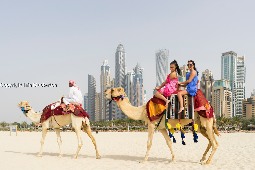 Tourists taking a camel ride on beach at Marina district of New Dubai in United Arab Emirates