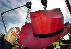 Ronny Bolton attaches a support clap to the rim of the 1,400 pound red cowboy hat that sits atop the Eiffile Tower in Paris, Texas Tuesday, April 18, 2006.  The eight year old Paris landmark is being taken down for cleaning and a fresh coat of paint.<br /> (AP Photo/The Paris News, Sam Craft)