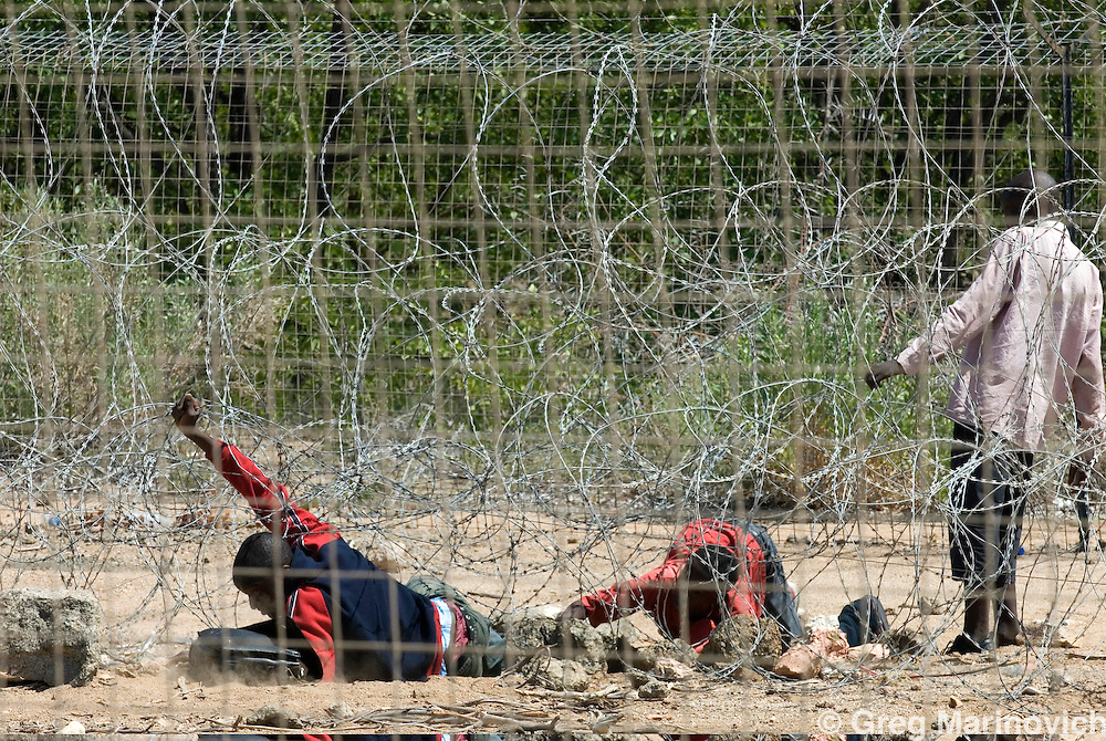 Zimbabwean teenagers Tareiro Mbudzi 19 (front in red and blue top) and Obey Sithole (centre) crawl under razor wire and then climb over the third and last fence from Zimbabwe to South Africa in their attempt to enter South Africa illegally to start a new life. The youth behind holding wire up is a guide they paid, but he robbed them at knifepoint of what they had, including spare shoes, music CDs etc March 20, 2007. Thousands of Zimbabweans attempt the crossing each day, some of whom are arrested by the security forces, the women are often raped, and all robbed or extorted.  Picture: Greg Marinovich
