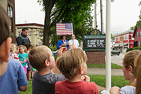 Holy Trinity Catholic School students wave American flags during a Memorial Day service held on the front lawn Friday morning.  (Karen Bobotas/for the Laconia Daily Sun)