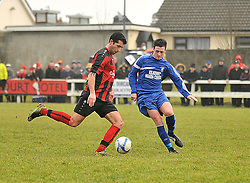 Westport United's Sean Tagg gets his clearance away despite Freebooters FC's  Paddy Cahill closing in.<br /> Pic Conor McKeown