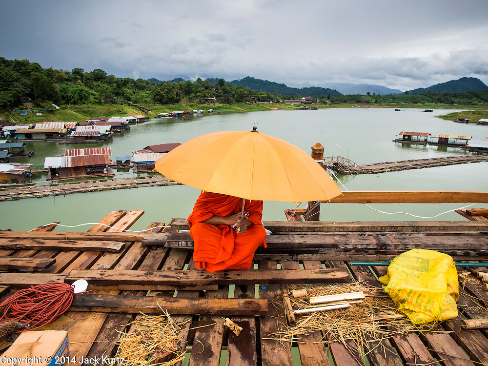 17 SEPTEMBER 2014 - SANGKHLA BURI, KANCHANABURI, THAILAND: A Buddhist monk from the Mon community sits on the Mon Bridge. The 2800 foot long (850 meters) Saphan Mon (Mon Bridge) spans the Song Kalia River. It is reportedly second longest wooden bridge in the world. The bridge was severely damaged during heavy rainfall in July 2013 when its 230 foot middle section  (70 meters) collapsed during flooding. Officially known as Uttamanusorn Bridge, the bridge has been used by people in Sangkhla Buri (also known as Sangkhlaburi) for 20 years. The bridge was was conceived by Luang Pho Uttama, the late abbot of of Wat Wang Wiwekaram, and was built by hand by Mon refugees from Myanmar (then Burma). The wooden bridge is one of the leading tourist attractions in Kanchanaburi province. The loss of the bridge has hurt the economy of the Mon community opposite Sangkhla Buri. The repair has taken far longer than expected. Thai Prime Minister General Prayuth Chan-ocha ordered an engineer unit of the Royal Thai Army to help the local Mon population repair the bridge. Local people said they hope the bridge is repaired by the end November, which is when the tourist season starts.    PHOTO BY JACK KURTZ