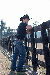 cowboy leaning on a wooden fence