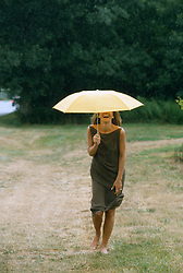 Woman enjoying the rain while under an umbrella in the countryside