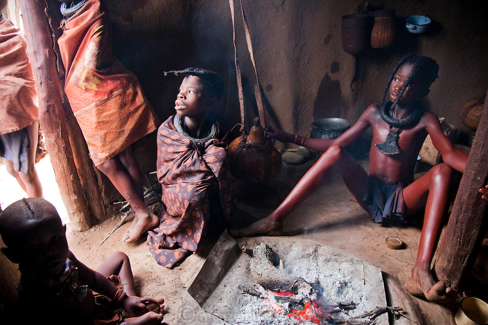 Traditionally dressed Himba boys and girls sit in a hut made of wood and earth in Okapembambu village, northwestern Namibia.