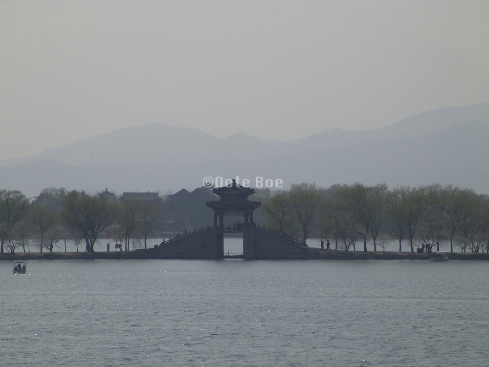 view over the lake at the Summer Palace with bridge and mountains in the distance Beijing