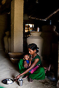 Pramila Tharu, 15, cradles her 2 year old toddler Prapti, in Bhaishahi village, Bardia, Western Nepal, on 29th June 2012. Pramila eloped and married at 12 and gave birth to Prapti at age 13. She delivered prematurely on the way to the hospital in an ox cart and her baby weighed only 1.5kg at birth. In Bardia, StC works with the district health office to build the capacity of female community health workers who are on the frontline of health service provision like ante-natal and post-natal care, especially in rural areas. Photo by Suzanne Lee for Save The Children UK