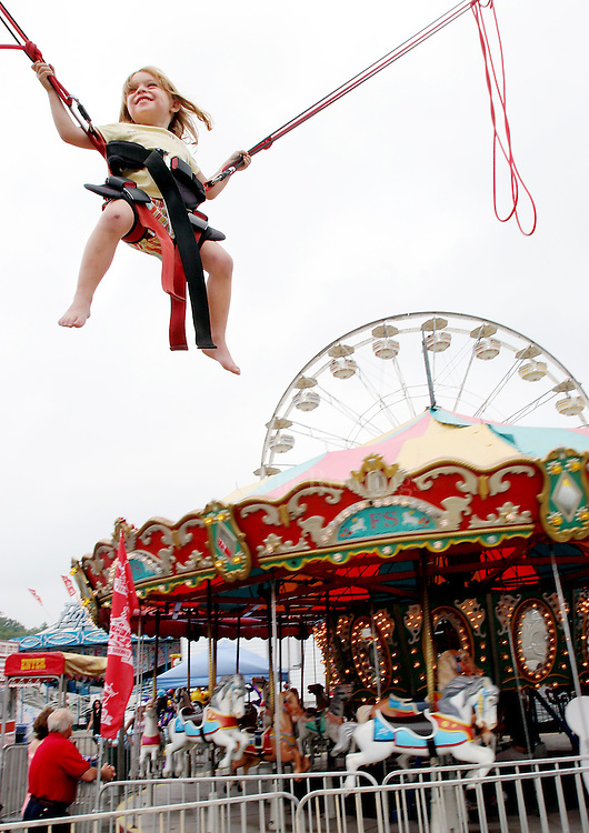 08/21/05 Marshfield, MA-- Jordan Pelissier, 3, of Whitman, soars above the rides at the Marshfield Fair Sunday while riding the Extreme Power Jump  (082105marshfieldar03, saved in mon, Staff Photo by Angela Rowlings)