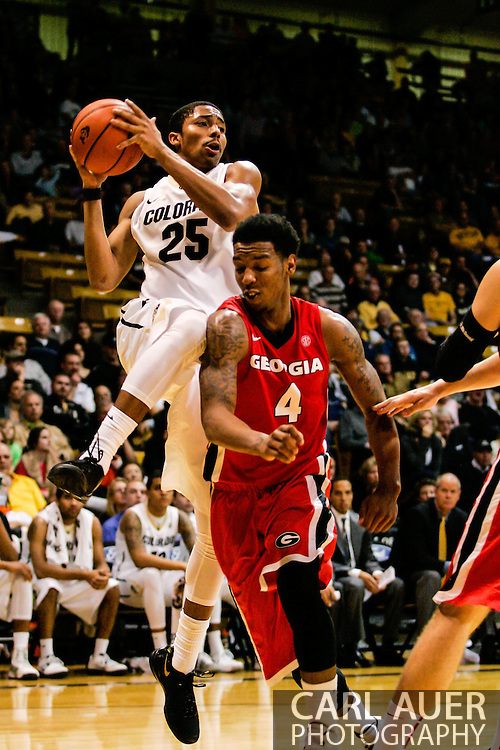 December 28th, 2013:  Colorado Buffaloes junior guard Spencer Dinwiddie (25) looks to pass the ball into the key over Georgia Bulldogs sophomore guard Charles Mann (4) in the second half of the NCAA Basketball game between the Georgia Bulldogs and the University of Colorado Buffaloes at the Coors Events Center in Boulder, Colorado