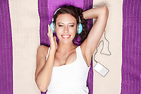 Happy woman listening to music through MP3 player using headphones while lying on picnic blanket